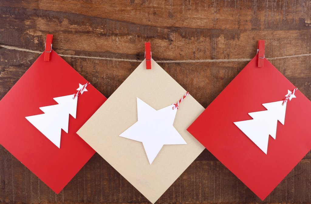 A strong with red pegs holding red and white christmas cards
