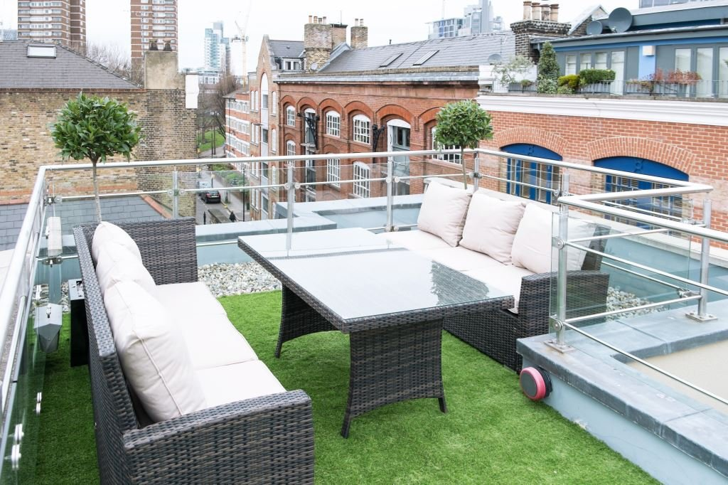 Roof terrace area with ratten furniture, artificial grass and two tree style plants.