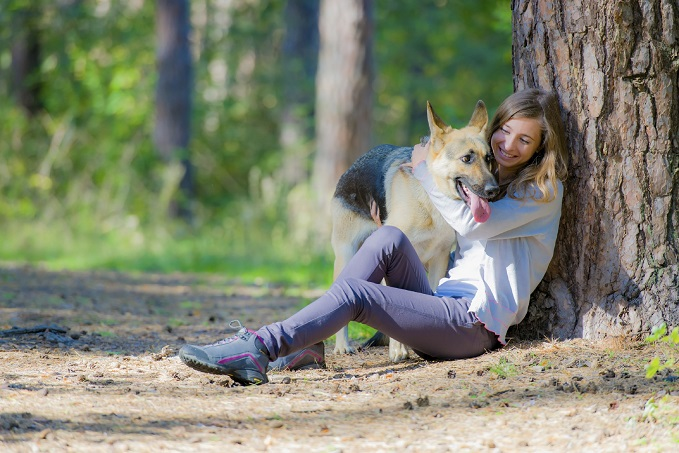 Woman forest bathing with dog. She is cuddling the German Sheppard and leaning against tree