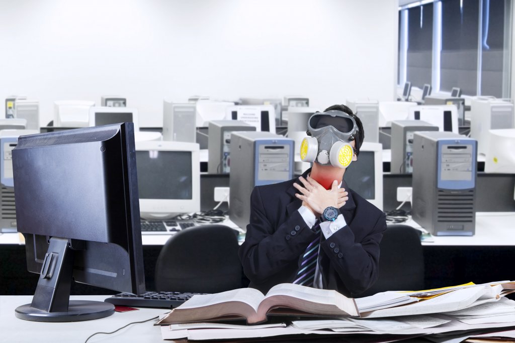 Man at desk in open plan office with gas mask on, clutching his red throat