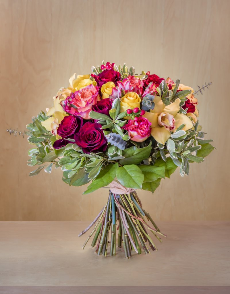 Flower bouquet tied together with ribbon 'standing' on table in front of wooden background