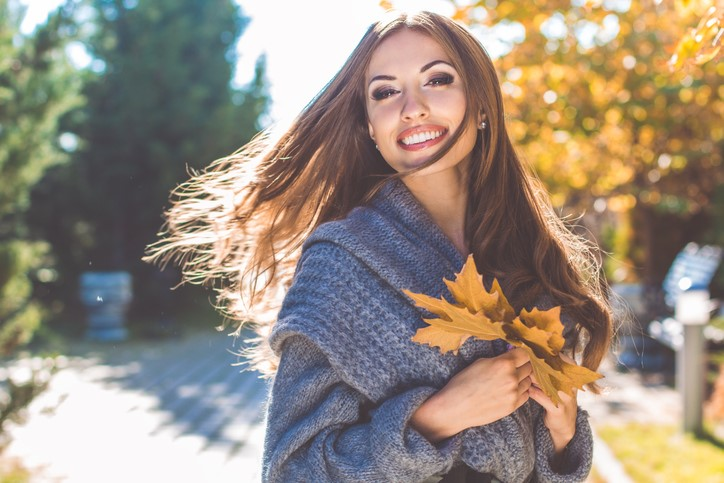Woman happily posing for camera holding fallen autumn leaves in what looks like a national park