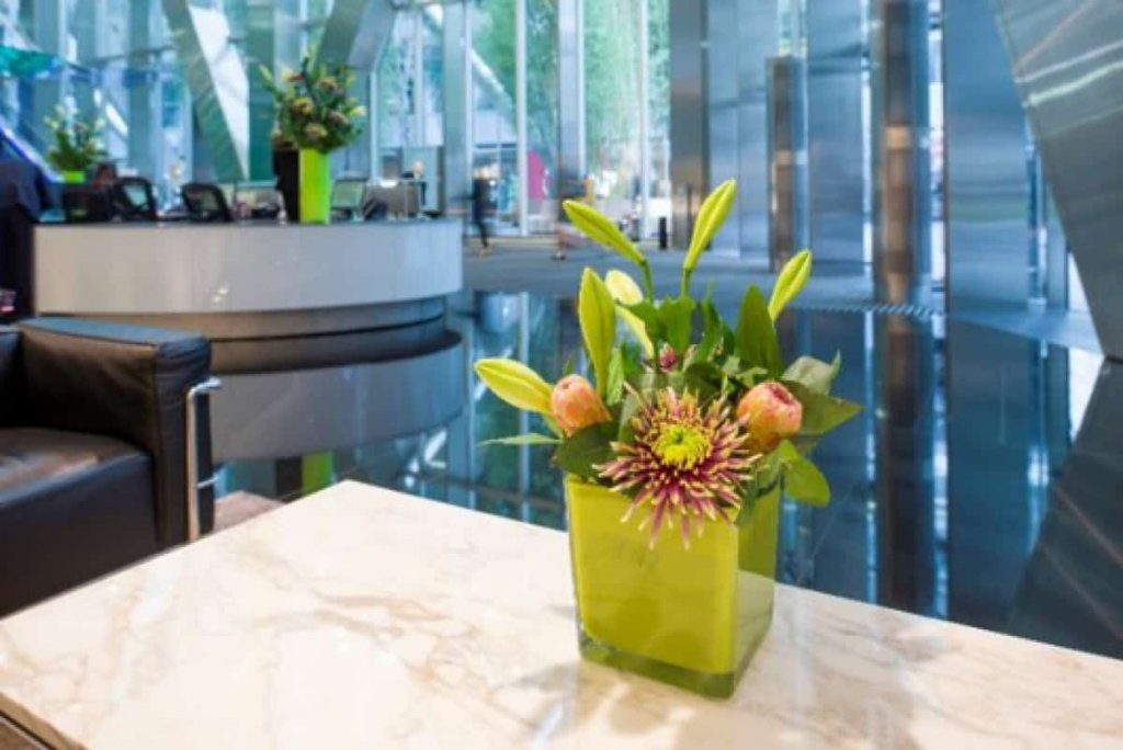 hotel lobby desk with bright green square vase and an arrangement of lily plants