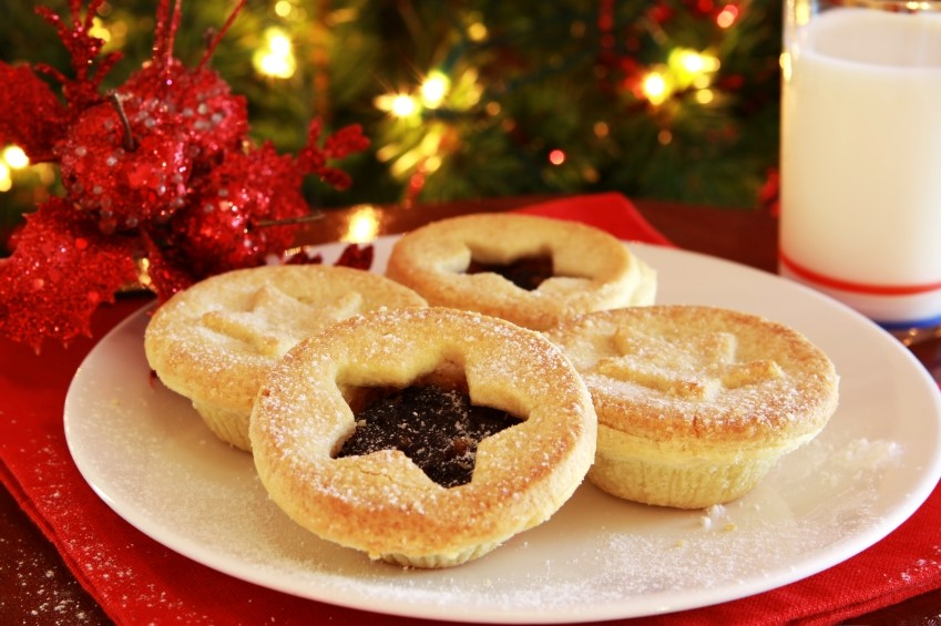 A plate of mince pies and a glass of milk in front of Christmas tree. Two mince pies have pastry toppings with stars embossed on them whereas the other two have stars cut into their pastry topping