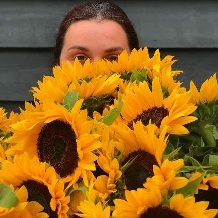 Woman hiding behind large bunch of sunflowers