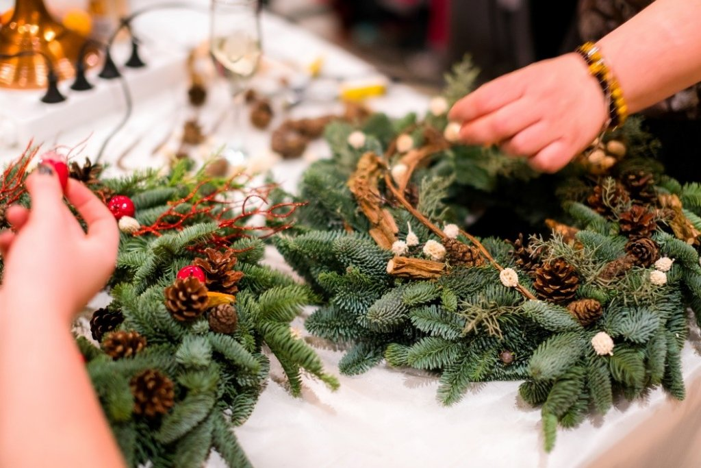 Close up of two people's hands while they make Christmas Wreaths