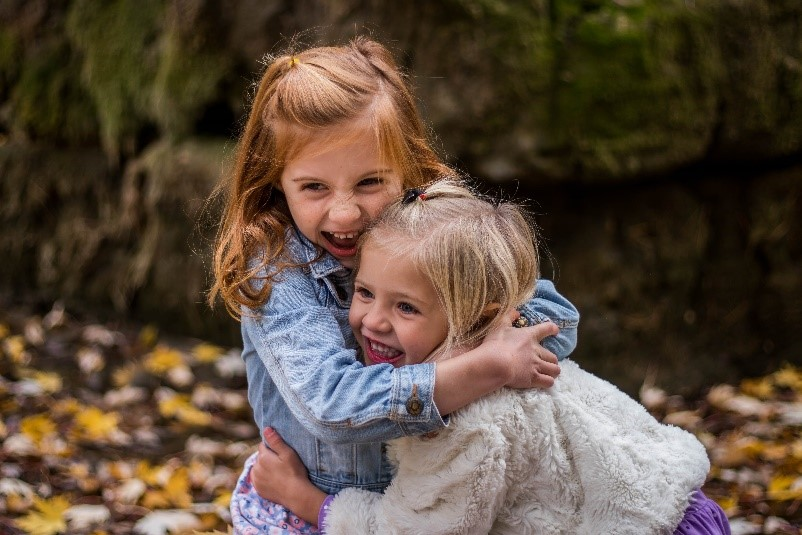 Two young girls cuddling and looking happy infront of rock wall and fallen leaves in a national park