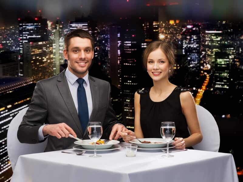 Couple eating meal in front of cityscape