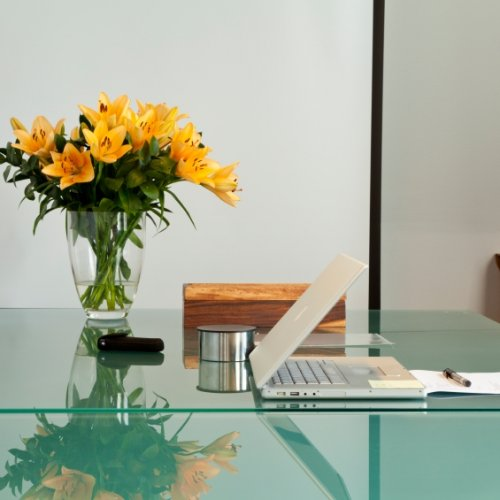 bouquet of yellow flowers and a laptop on an office desk